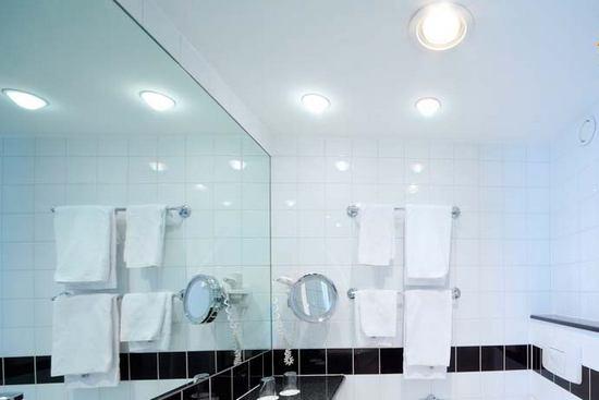 Ванная комната с белыми стенами и освещением верхним