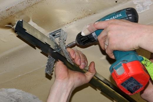 Крепление стрингеров к подвесам при монтаже реечного потолка в ванной комнате