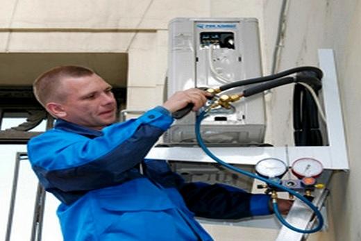 Специалист сервисной службы заправляет фреоном кондиционер