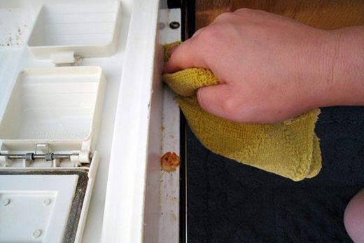 Дверь посудомоечной машины протирают мягкой тряпкой, фото