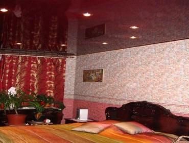 Натяжной потолок бардового цвета выглядит строго в спальне