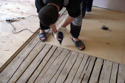 В старом деревянном полу при помощи фанеры закрываем щели
