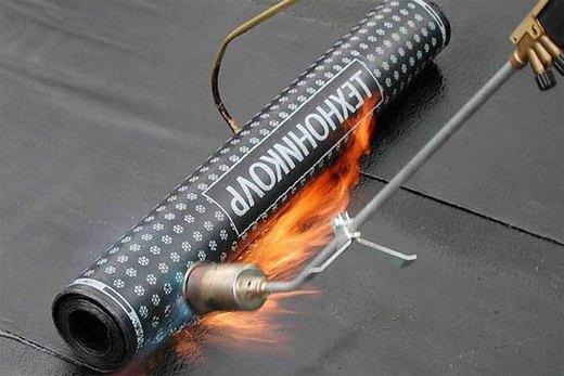 Для гидроизоляции пола нагреваем материал горелкой