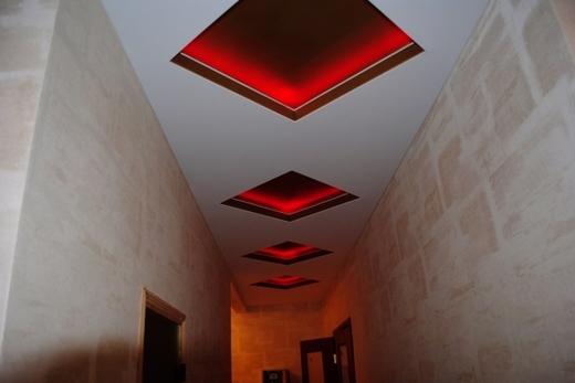 На потолке словно указывают путь гостю алые ромбы